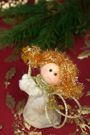 Little angel dolls and a twig of spruce in background, shallow DOF photo