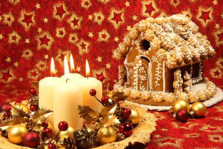 Christmas decoration with four candles and gingerbread house on red Christmas background. Shallow DOF, copy space photo