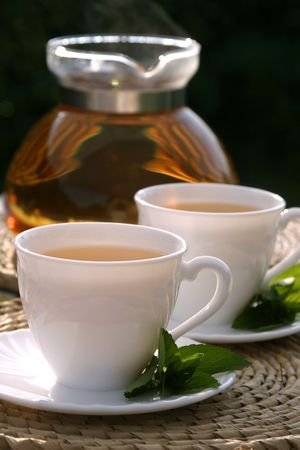 Freshly made mint tea with mint leaves and teapot photo