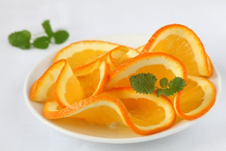 Orange slices on a plate and white background. Shallow dof photo