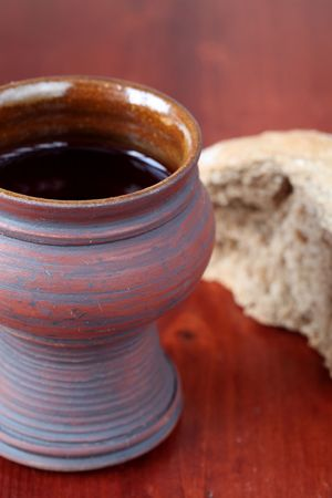 Communion chalice with red wine and bread. Shallow dof, copy space photo