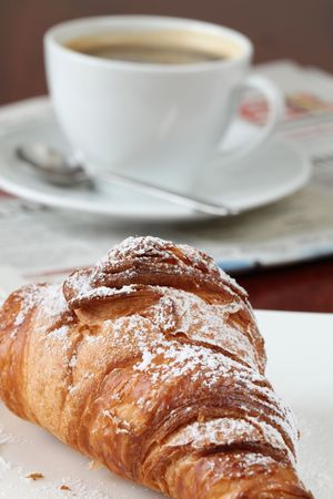 Croissant, coffee and newspaper photo