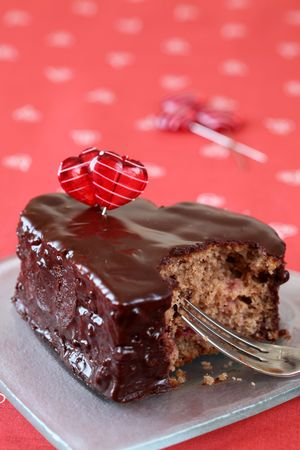 Heart shaped chocolate cake with heart pins and a bite photo