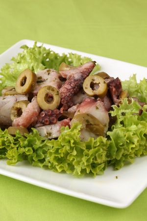 Octopus salad with green olives and lettuce photo