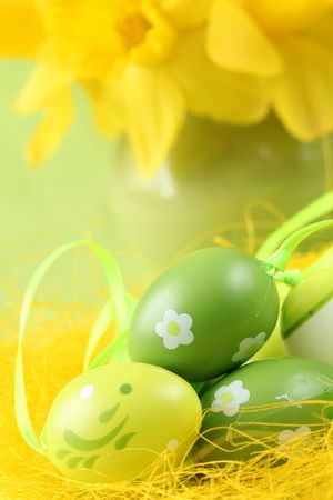 Green Easter eggs and yellow daffodils photo