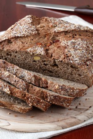 breadloaf: Loaf of wholemeal bread with slices on cutting board Stock Photo