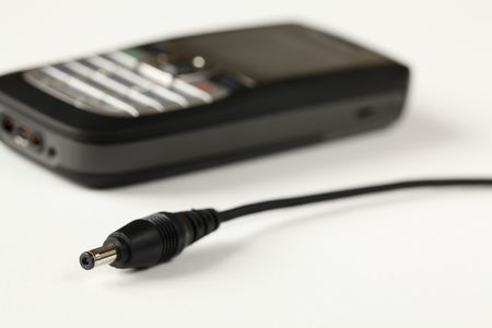 Cell phone charger and cell phone on white background.  photo