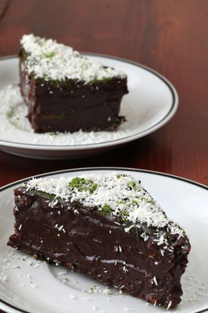 Chocolate cake garnished with coconut and Matcha green tea powder photo