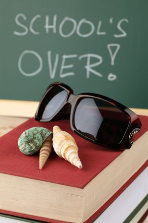 Sea shells and sunglasses on a pile of books and a chalkboard in background with text: School is over photo