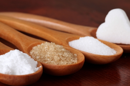 sugar: Wooden spoons with different kinds of sugar