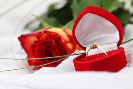 Golden engagement ring in a heart shaped box and rose. White background, shallow DOF photo