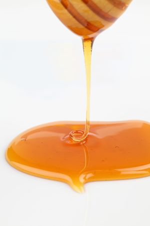 Close up of pouring honey on white background Stock Photo