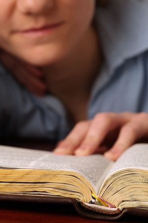 Young woman reading the Bible. Focus on the Bible photo