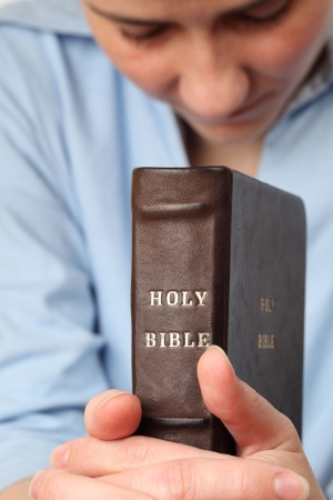 humbled: Young woman holding the Bible and praying Stock Photo