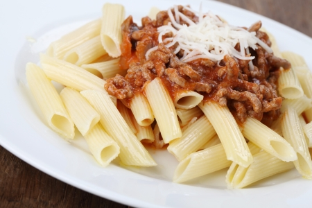 Penne pasta with bolognese sauce and cheese photo