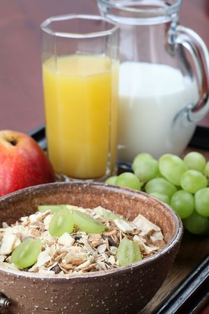 Healthy breakfast consisting of granola, grapes, apple, orange juice and milk photo