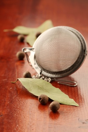 Allspice, bay leaf and tea strainer on a wooden background photo