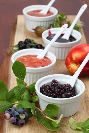 Blueberry, nectarine, black currant and gooseberry jams on a wooden board photo