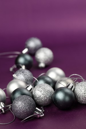 Silver Christmas ornaments on purple background. Copy space