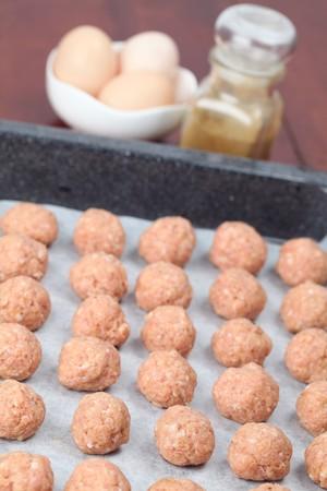 Raw meatballs on baking sheet, ready for roasting. Shallow DOF photo