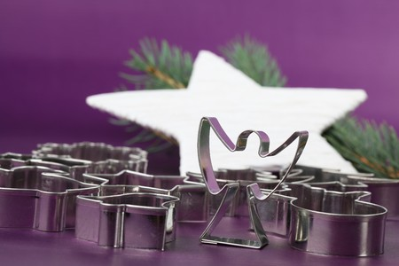Angel shaped cookie cutter and other cutters on Christmas background photo