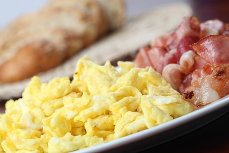 Scrambled eggs and slices of bacon on a plate photo
