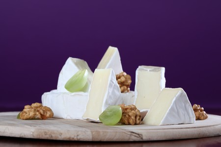 Camembert cheese on cutting board with walnuts and grapes photo