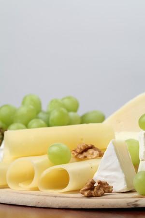 tabla de quesos: Diversos tipos de queso con nueces y uvas