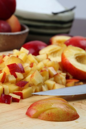 Halved and chopped nectarines on a cutting board for jam making photo