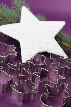 Various shaped cookie cutters on Christmas background photo