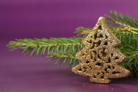 Golden ornament in the shape of Christmas tree on purple background