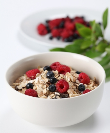 Granola with fresh organic raspberries and blueberries. Shallow DOF photo