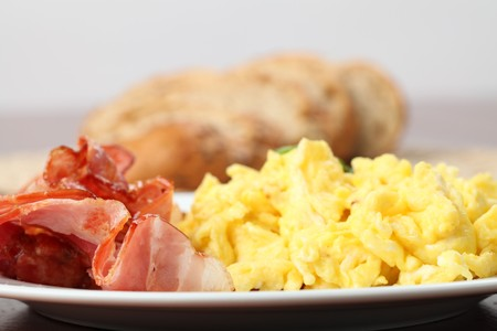 scrambled eggs: Huevos revueltos y rebanadas de tocino en un plato  Foto de archivo