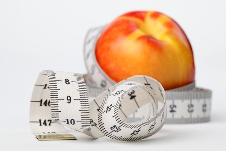 Tape measure and nectarine. Focus on tape measure