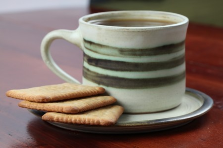 Biscuits and a cup of coffee. Focus on biscuits. Shallow DOF photo