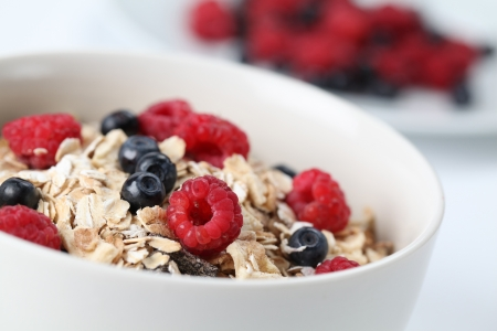 cereal bowl: Granola with fresh organic raspberries and blueberries. Shallow DOF Stock Photo