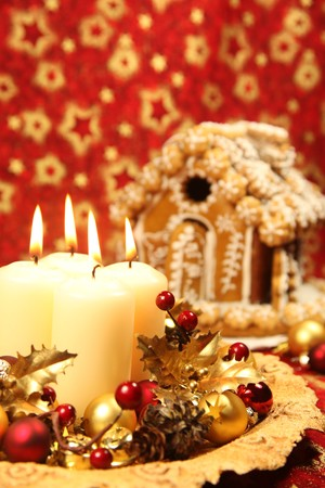 Christmas decoration with four candles and gingerbread house on red Christmas background. photo