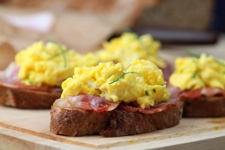 Sandwiches with scrambled eggs and bacon, garnished with chives. photo