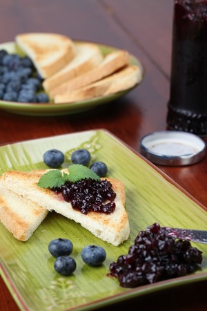Toasts with blueberry jam and fresh blueberries. Shallow dof photo