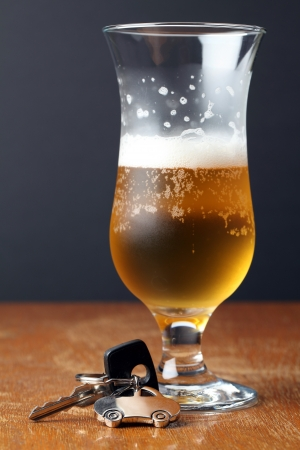 drink and drive: Car key with car-shaped pendant and a glass of beerDrinking and driving concept. Stock Photo