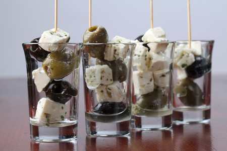Greek appetizers in small glasses with black and green olives and feta cheese photo