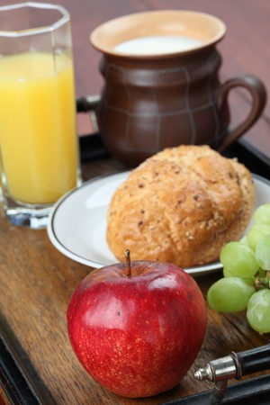 Healthy breakfast consisting of fresh fruits, wholemeal bread, orange juice and milk photo