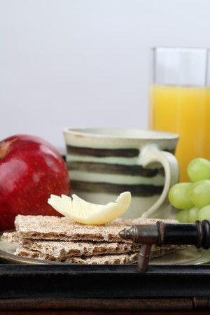 Healthy breakfast consisting of fresh fruits, crackers with butter, orange juice and tea or coffee photo