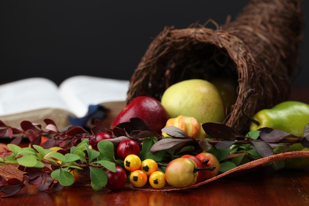 cuerno de la abundancia: Arreglo de acción de gracias con cornucopia y la Biblia en segundo plano  Foto de archivo