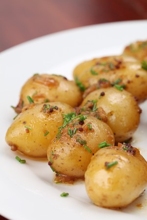 Roasted baby potatoes with onion, mustard seed and chives Stock Photo