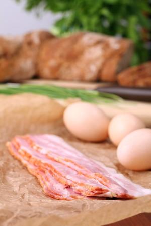 waxed: Bacon y huevos en papel encerado con cebollino y pan en segundo plano. Ingredientes para delicioso desayuno. Kelvin superficial.