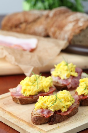 Sandwiches with scrambled eggs and bacon, garnished with chives. Shallow dof photo
