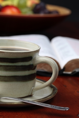 Morning coffee with the Bible and fruits in background. Shallow dof
