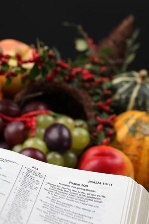salmo: Bibbia aperta al Salmo 100 con testo di ringraziamento e cornucopia in background.