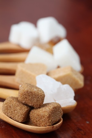 Sugar collection - various kinds of sugar cubes on wooden spoons. Shallow dof